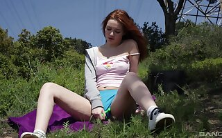 Solo redhead model Shelley Bliss plasy with her slit in outdoors