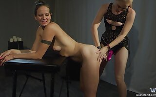 Submissive teen babe abused by a girl with a strap on in bondage